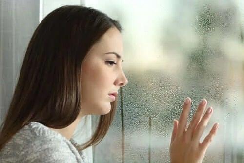 Femeie tristă care se uită pe geam