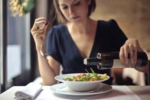 Femeie care toarnă ulei peste salată
