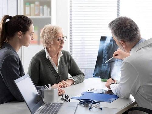 Medic explicând simptomele metastazelor osoase unor pacienți