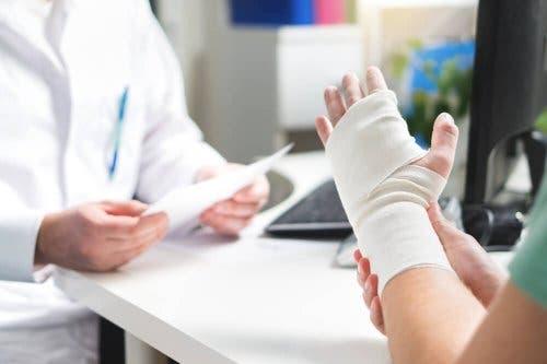 Pacient cu mâna fracturată discutând cu un medic