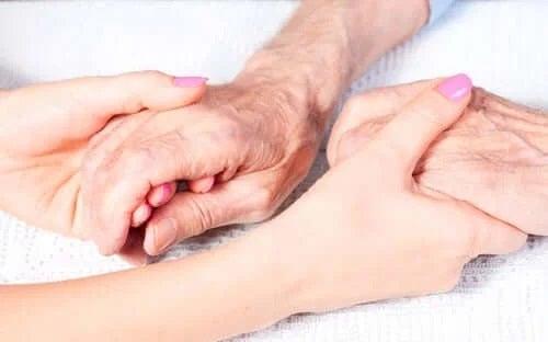 Tânără care ține mâinile unei bătrâne