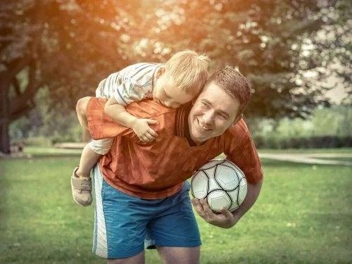 Bărbat care se joacă cu un copil cu mingea