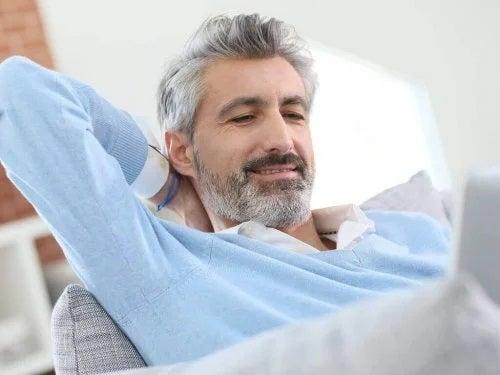 Bărbat cu părul alb care stă relaxat pe canapea