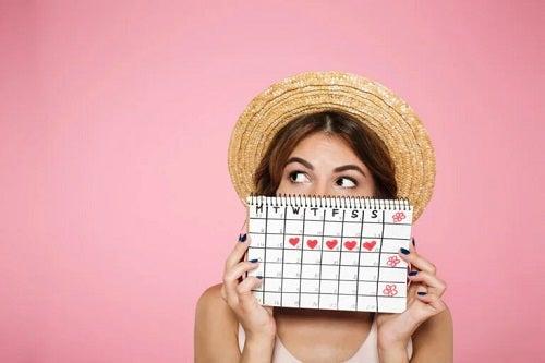 Fată care ține în mână un calendar menstrual