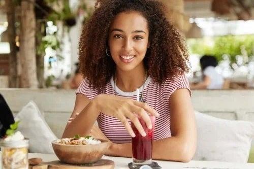 Fată care consumă un smoothie bowl la micul dejun