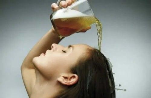 Femeie care își toarnă bere în păr