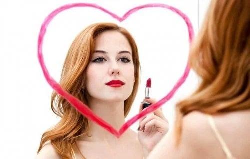 Femeie care desenează o inimă pe oglindă