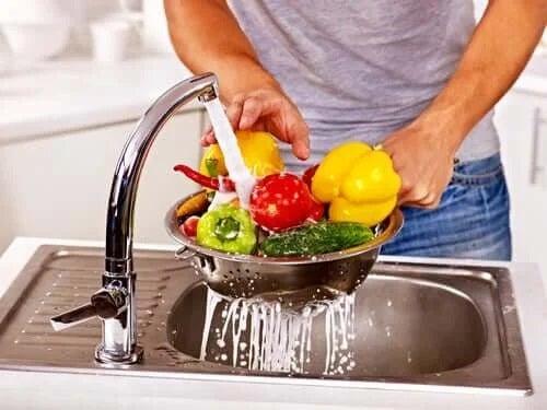 Bărbat care spală fructele la robinet