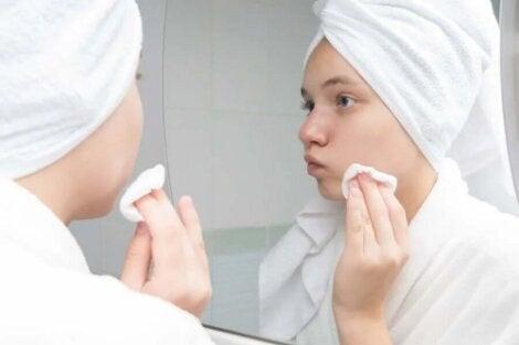 Tânără care se privește în oglindă