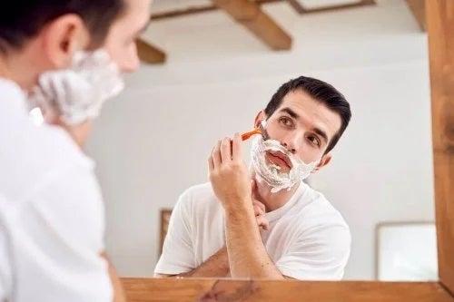 Bărbat care se bărbierește în oglindă