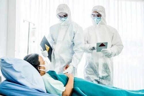 Bolnav pe patul de spital vizitat de medici în PPE