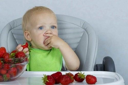 Copil care mănâncă căpșuni
