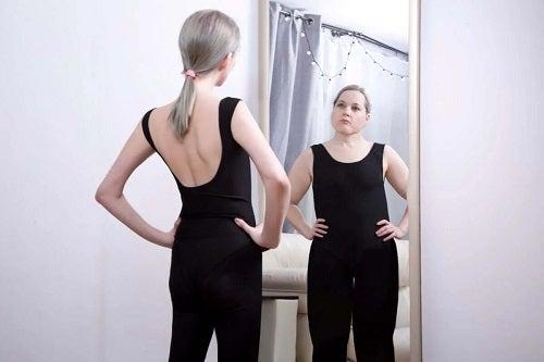 Fată care se vede grasă în oglindă