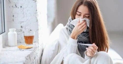 Femeie răcită care își suflă nasul