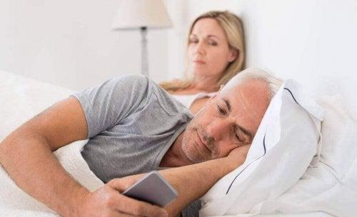 Femeie privindu-și soțul care își butonează telefonul mobil