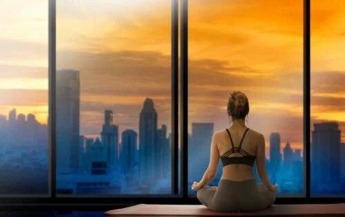 Femeie care face yoga în fața geamului