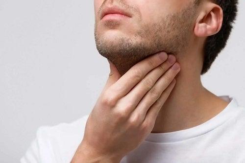 Bărbat care are o durere în gât
