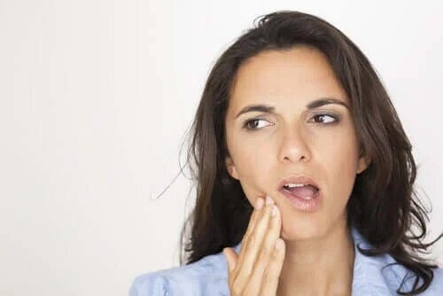 Femeie care simte durerea provocată de dinții sensibili