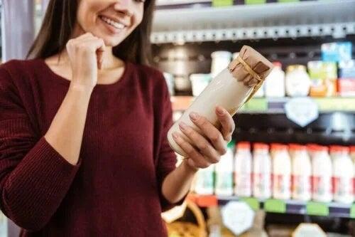 Femeie care citește eticheta unei sticle de lapte