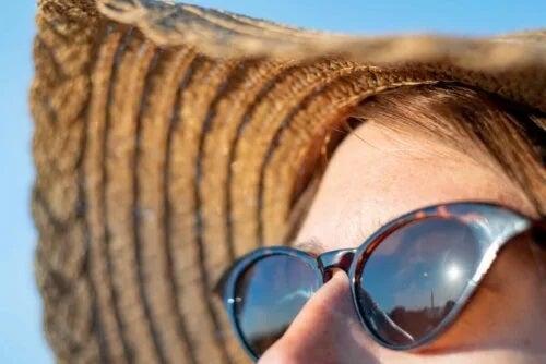 Femeie la plajă cu pălărie și ochelari de soare