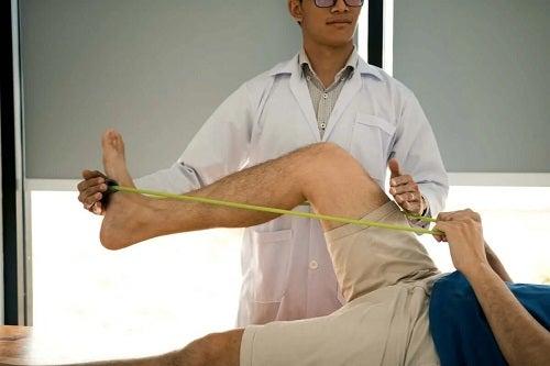Terapeut care antrenează un pacient cu benzi elastice