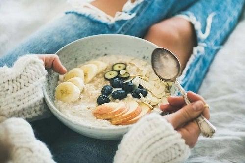 Fată care mănâncă ovăzul la micul dejun