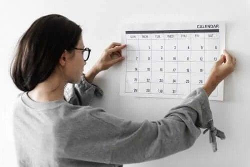 Femeie care pune un calendar pe perete