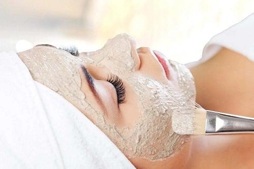 Femeie căreia i se aplică o mască facială