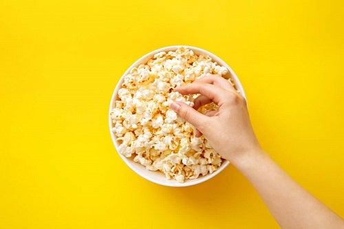 Mână luând popcorn dintr-un castron