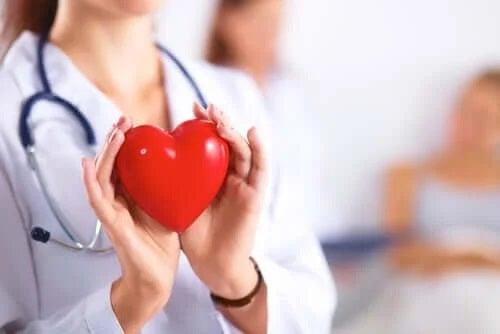 Medic care ține în mână o inimă roșie