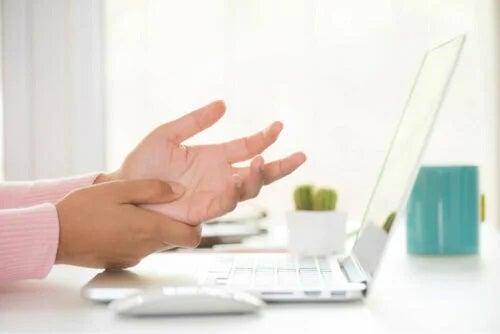 Persoană cu mâinile amorțite la laptop