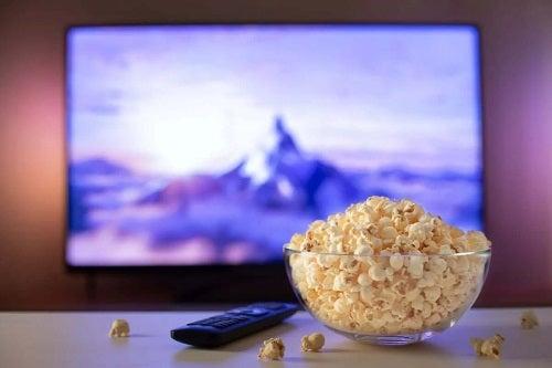 Castron cu popcorn în fața televizorului