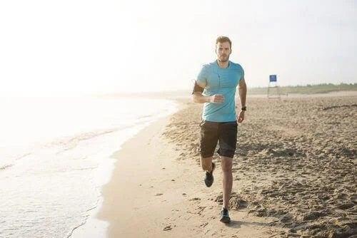 Bărbat care aleargă pe plajă