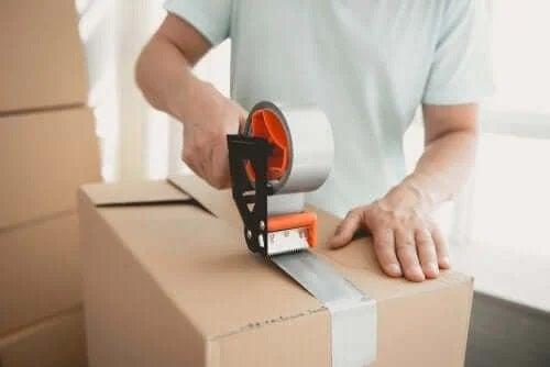 Bărbat care lipește cutii