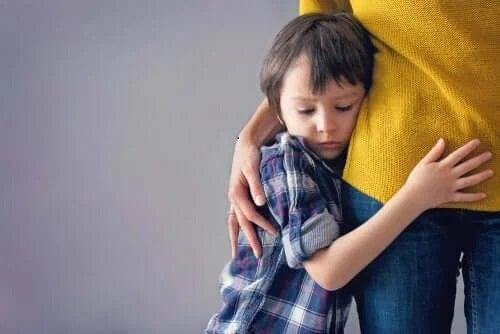 Copil care se ține de mama lui