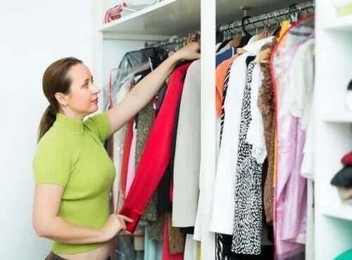 Femeie care se confruntă cu acumularea de haine în dulap