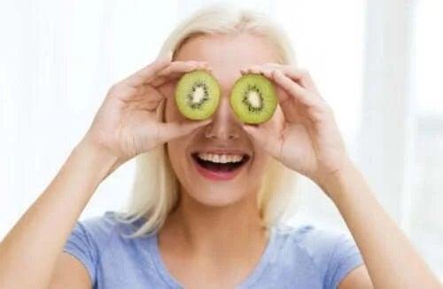 Femeie care ține felii de kiwi pe ochi
