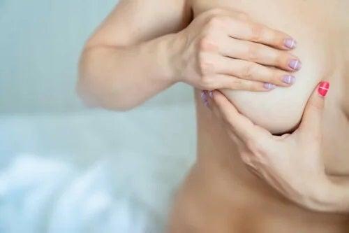 Femeie care își examinează sânul
