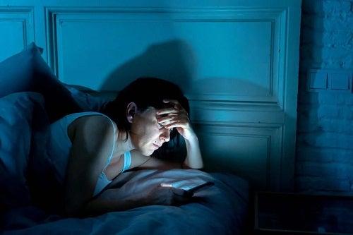 Femeie care butonează telefonul noaptea