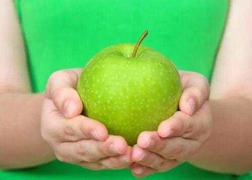 Persoană care ține un măr verde