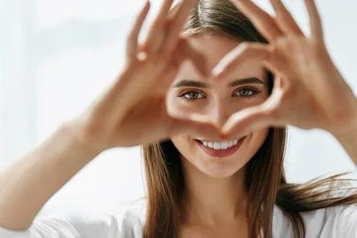 Fată care face cu mâinile o inimă