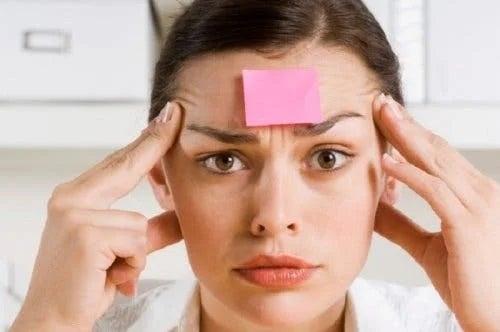 Femeie care are o notă adezivă pe frunte