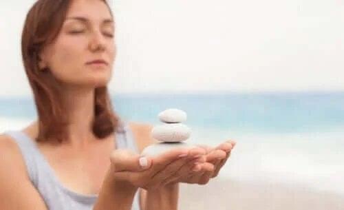 Femeie care adună pietre de pe plajă