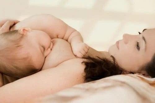 Mamă care își ține copilul pe piept