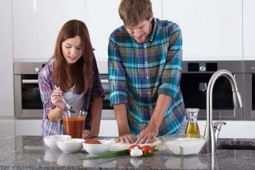 Cuplu ce prepară o rețetă de pizza napoletană