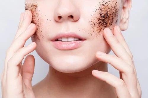 Femeie care își exfoliează fața cu zaț de cafea