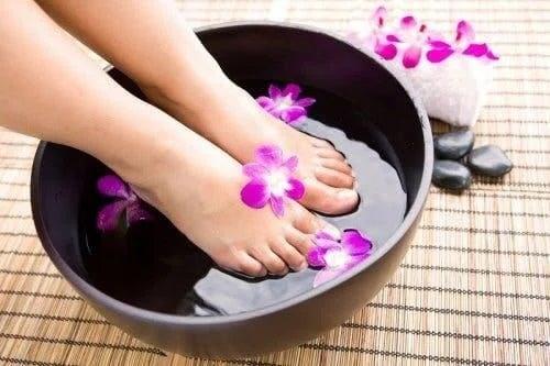 Femeie care își înmoaie picioarele care miros urât