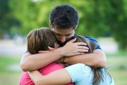 Părinte care își îmbrățișează copiii