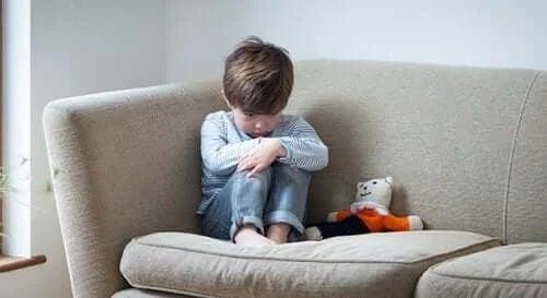 Copil trist stând e canapea