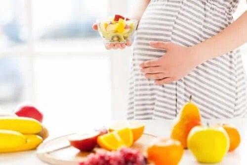 Gravidă care consumă fructe